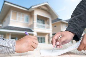 שתי ידיים חותמות על חוזה על רקע בית